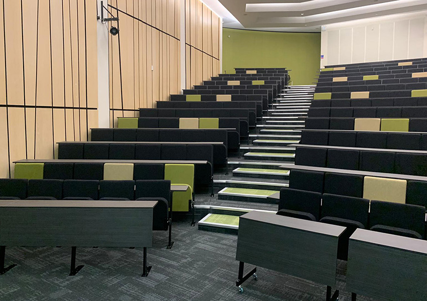 Lecture chairs with rows of fixed desks in large university lecture theatre