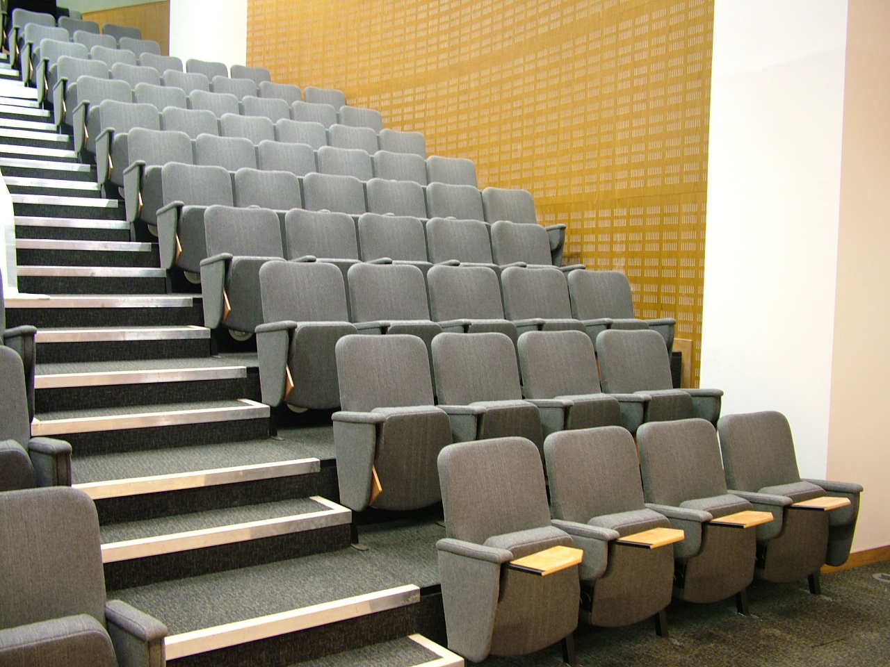 Lecture chairs with fold-away writing tablets in large university lecture theatre