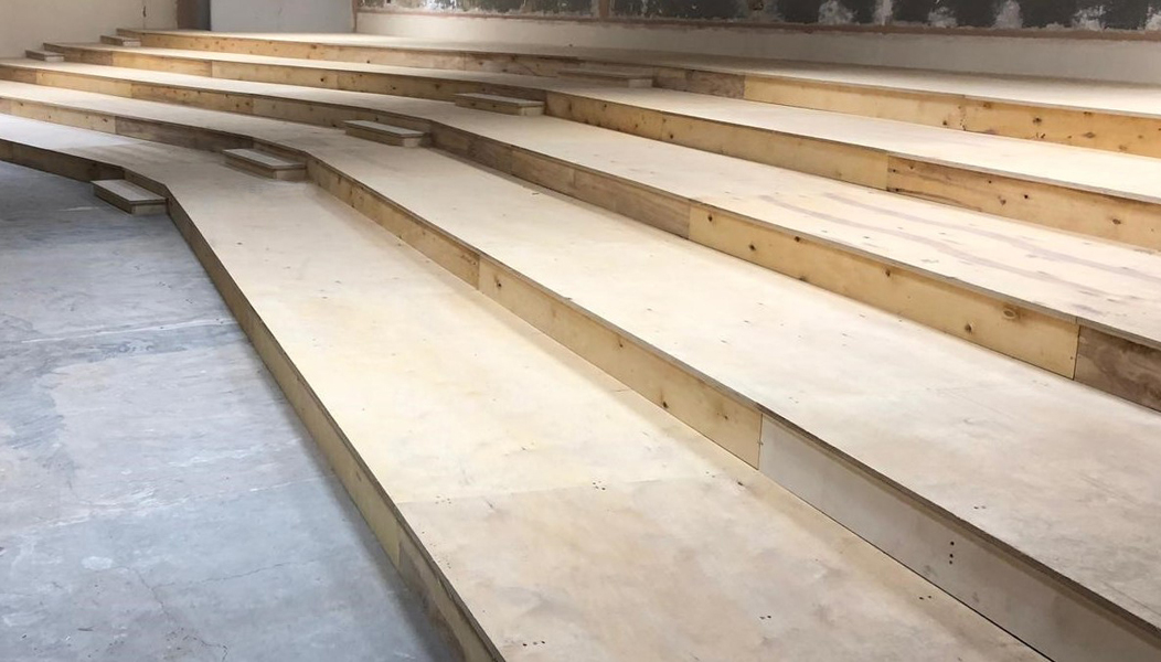 Wooden tiered floor structure in small lecture room prior to carpeting