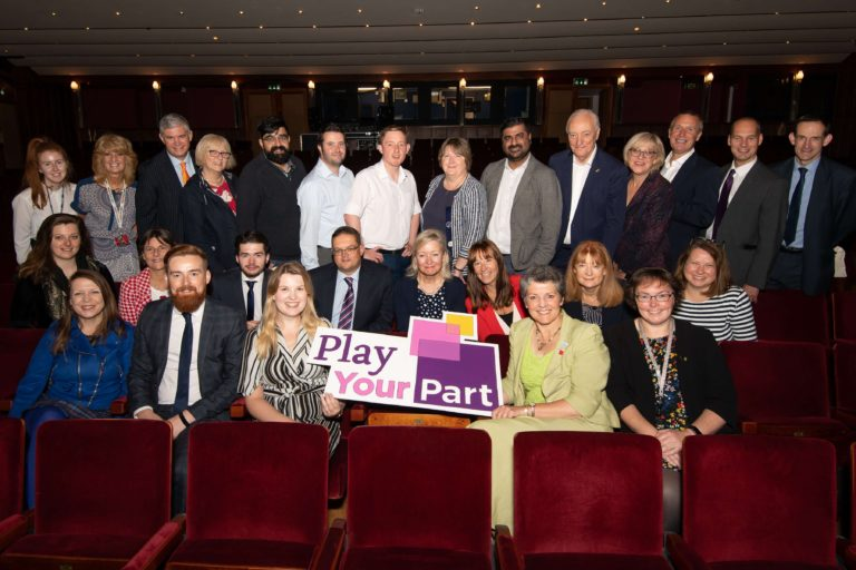 Representatives from businesses local to the Belgrade Theatre amongst the newly refurbished theatre seats holding a banner promoting the theatre's Play Your Part fundraising campaign
