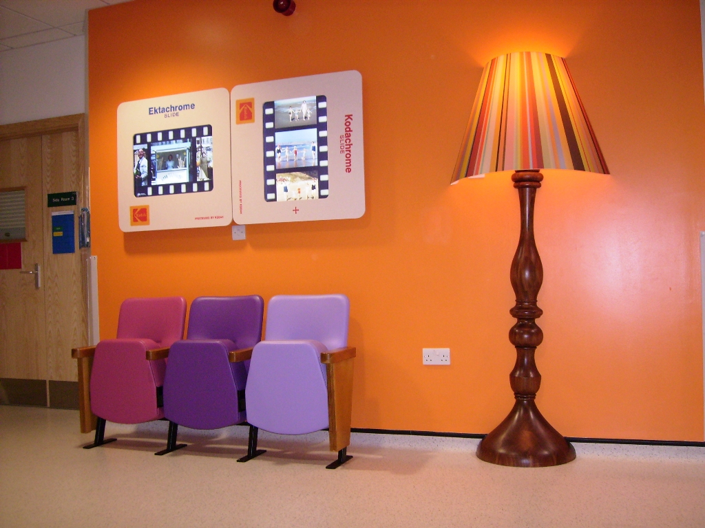 Hospital corridor with orange wall and 3-seat beam seating in pink and purple