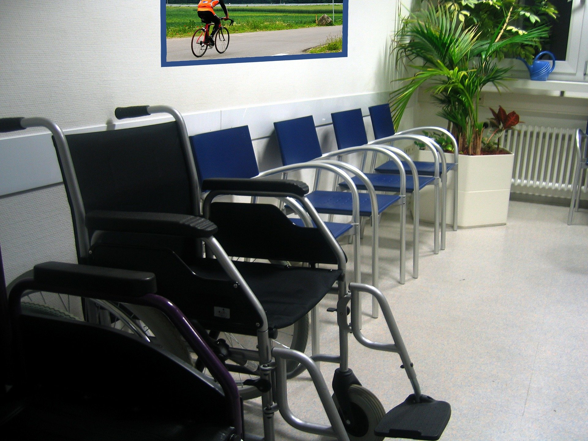 Healthcentre waiting room with blue plastic chairs and wheelchairs