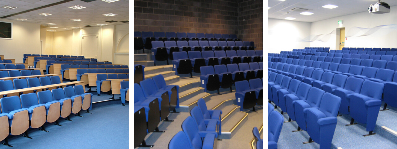 Blue auditorium seats shown with beech seat boards and desks, black seat boards and fully upholstered