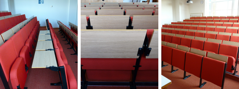 University lecture theatre with rows of fixed lecture seating with individual fold down desks