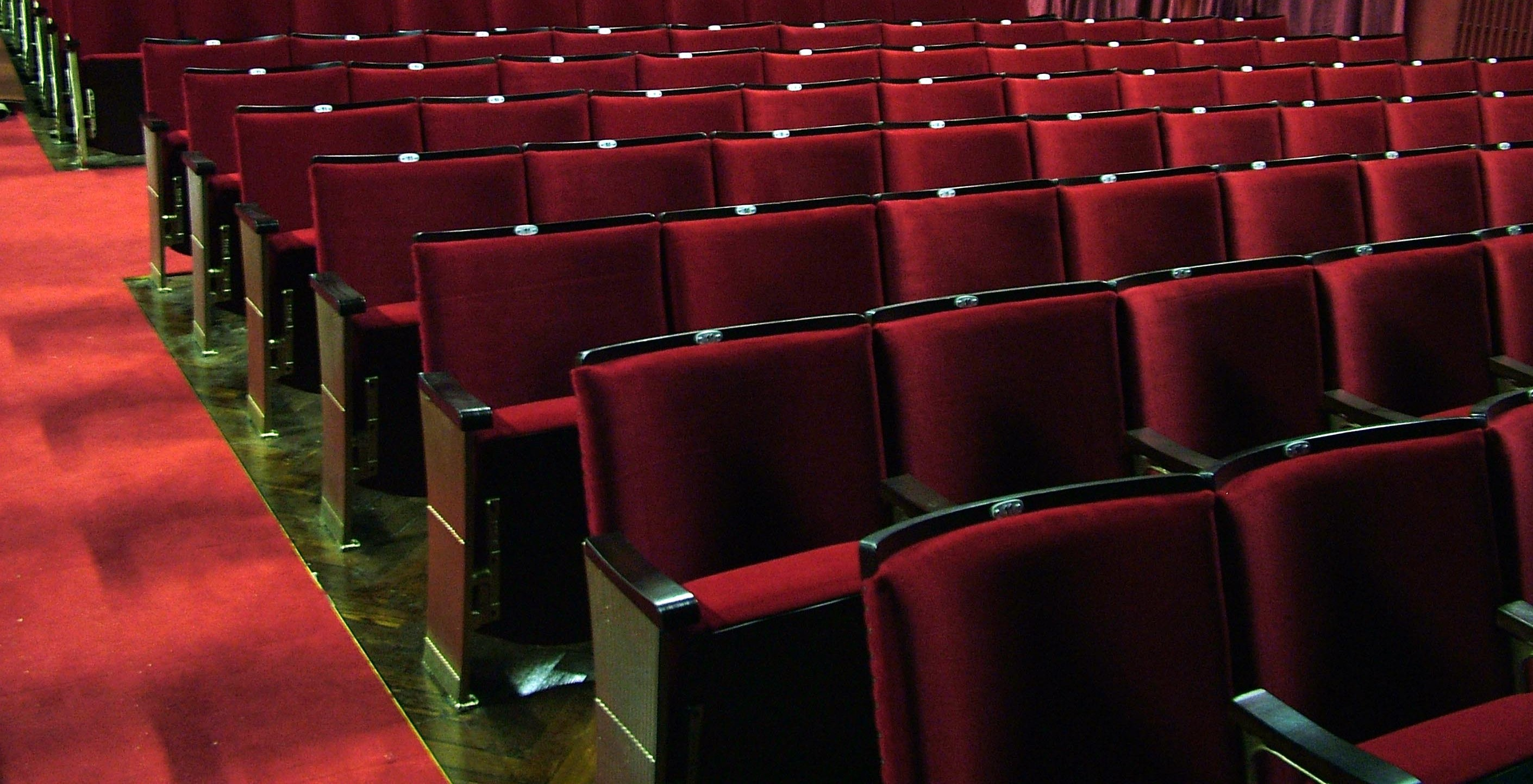 Traditional fixed seating in a theatre auditorium following reupholstery in red velvet fabric