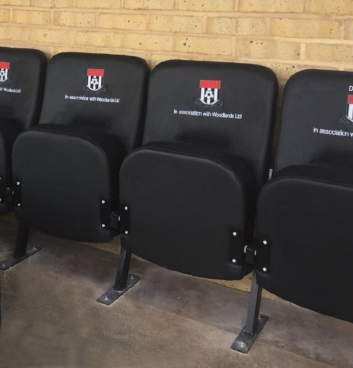 Row of branded upholstered stadium seating at Flint Town Utd FC