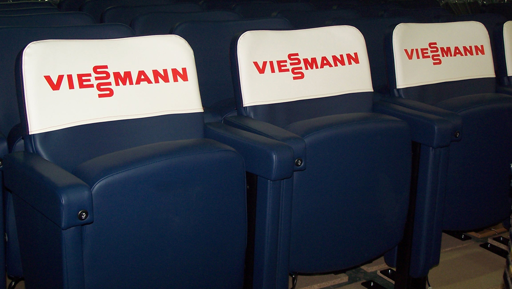 Row of upholstered stadium seating with branded removable covers